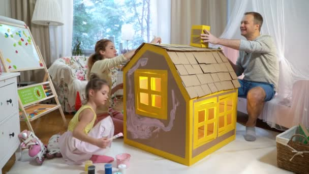 Young Family With Child Building And Painting Toy Cardboard House Together Stock Video