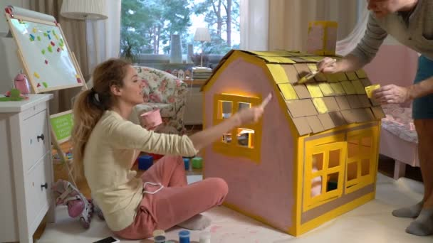 Young family with child building and painting toy cardboard house together.