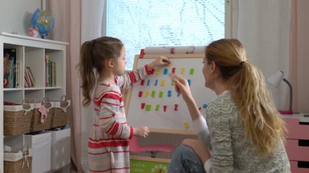 Rozvoj v raném dětství. Mladá žena učí své dítě abecedy