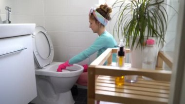 Woman with a rubber glove cleans a toilet bowl