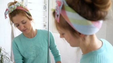 Woman with a rubber glove cleans a sink in the bathroom