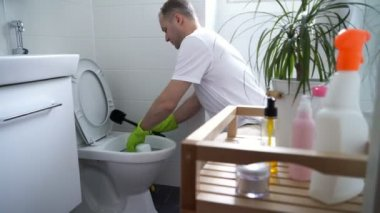 Man with a rubber glove cleans a toilet bowl