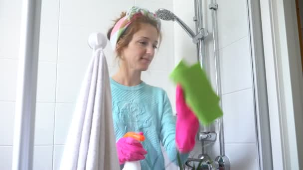 Frau mit Gummihandschuh reinigt Duschkabine