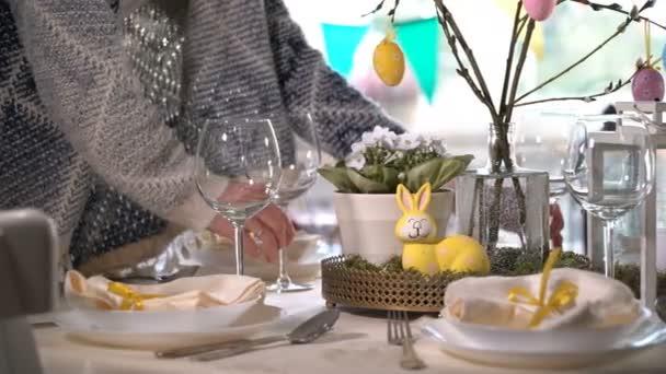 Junge Frau, die festlichen Ostertisch mit Hasen und Eiern Dekoration festlegen