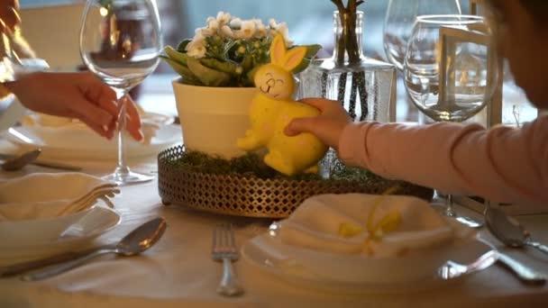 Nő és vele a kis lányom állítunk húsvéti nyuszi és tojás díszítéssel ünnepi asztal