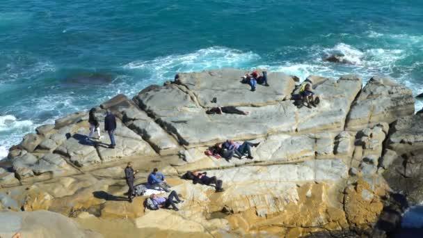 Az emberek élvezik a napsütést és a hullámok a part menti sziklákon
