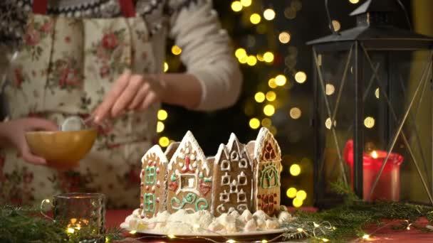 Egy fiatal nő cukormázat szórt a mézeskalács házra.