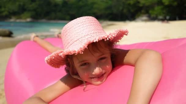 Holčička v růžovém slamáku ležící na nafukovací pohovce na pláži