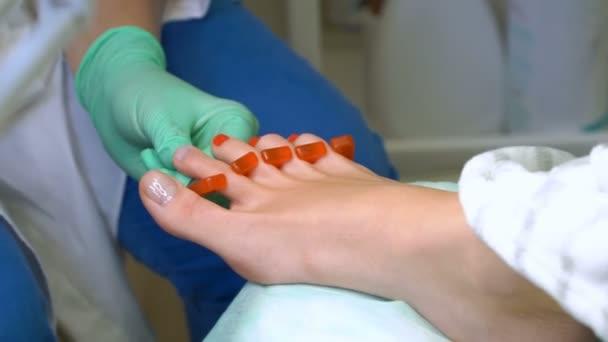 Pedikérka lakuje mladé ženy nehty na nohou