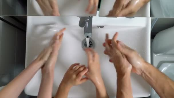 Family couple with child washing hands in bathroom at home