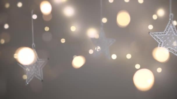 Vánoční krajkové ozdoby ve tvaru hvězd s rozostřenými světly v popředí a na pozadí. Výstřel v rozlišení 4K. Mělká hloubka pole.