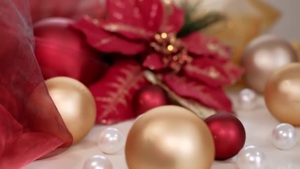 Vánoční skladba ve zlatých a červených tónech s květinami a cetkami Poinsettia. Dolly shot rozlišení 4K.