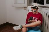 Fényképek gyermek otthon a mobiltelefonnal