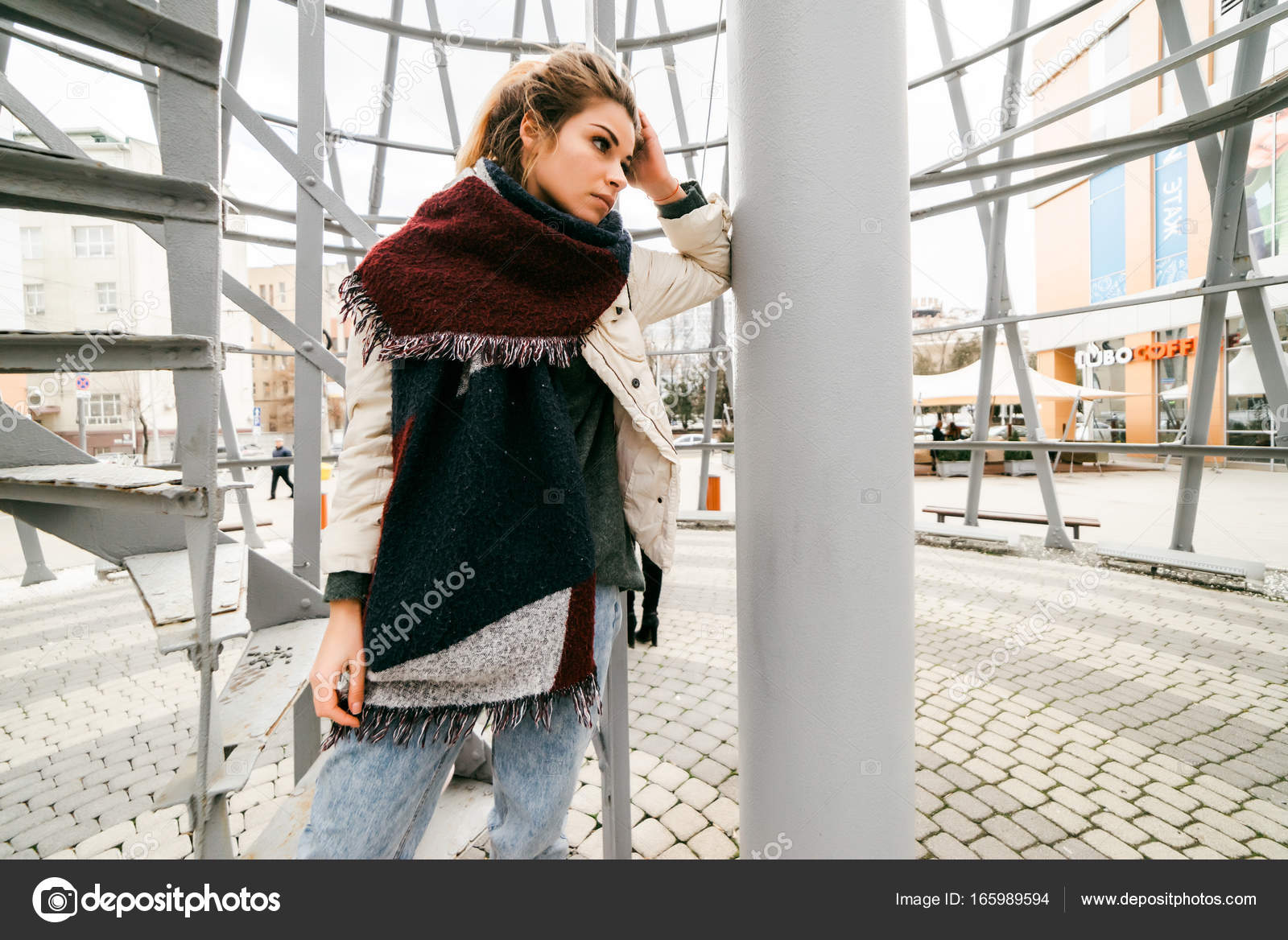 A Beautiful Girl In A Scarf With Blond Hair Pondered Leaned Against A Pillar In The Building Against The Backdrop Of A Staircase Photo By