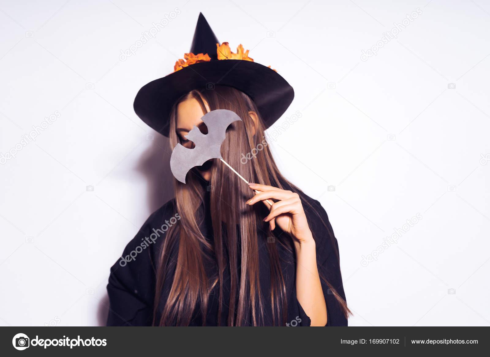 La strega di Halloween con un vestito nero e un grande cappello con foglie  di arancio è che tiene una mazza mazza sulla sua mano e nasconde il suo  volto con ... 75c433774b8b