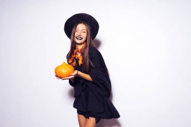 young gothic sexy girl in the image of a witch celebrates halloween, holds a pumpkin in his hands