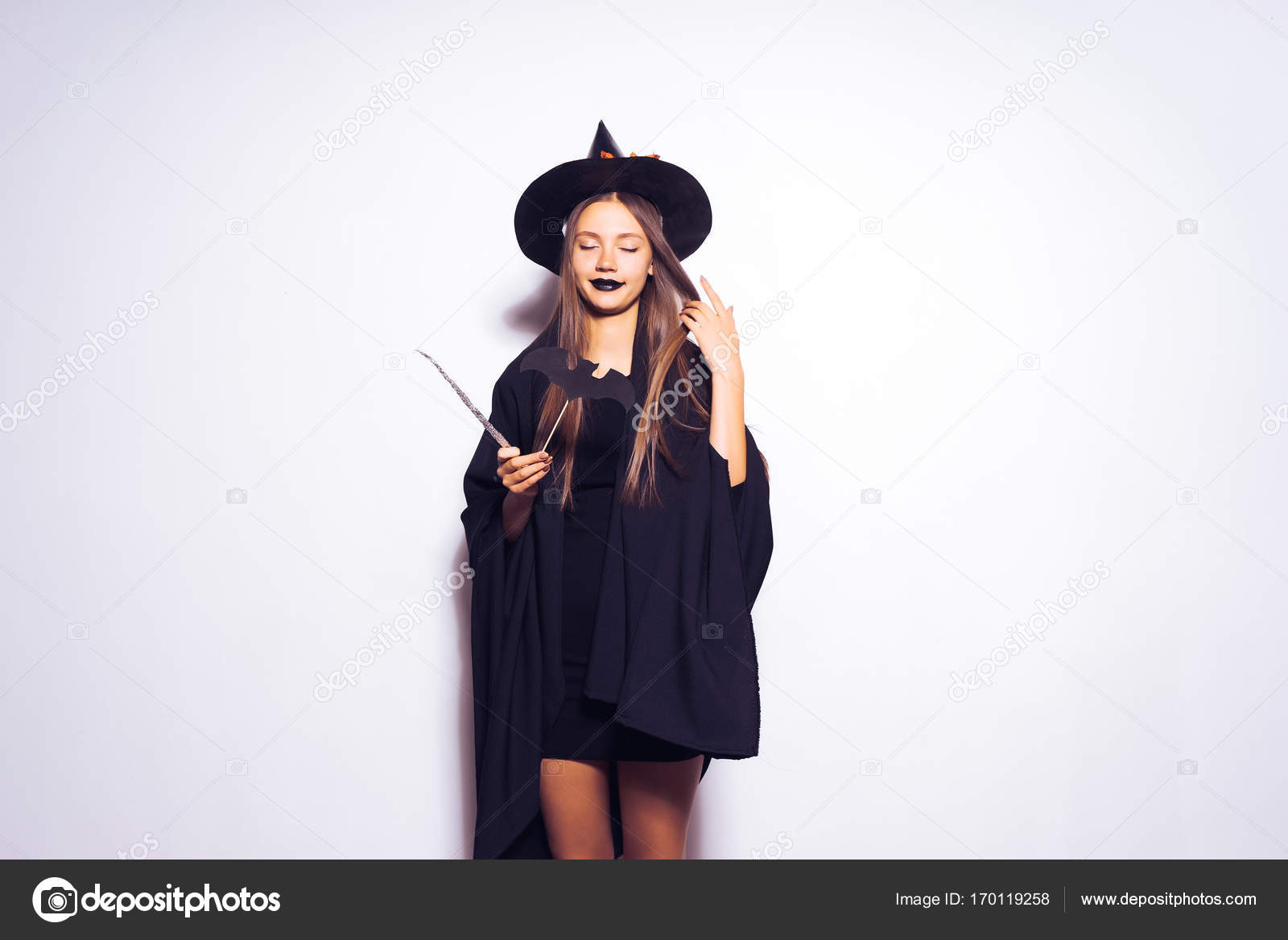 A young sexy gothic girl dressed in a witch for Halloween, holds in her  hands a magic wand– stock image