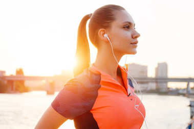 The girl in sports clothes went for a run on the embankment at sunset. A girl listening to music on a run
