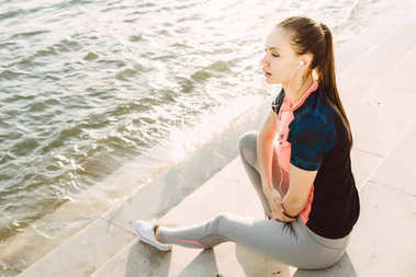 A young athletic girl running, in the evening by the river, listening to music on headphones, resting by the water
