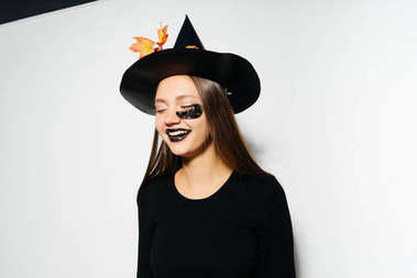 girl in a witch suit smiling on a white background