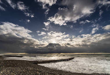 near a rocky beach the sea rages against the blue sky and clouds