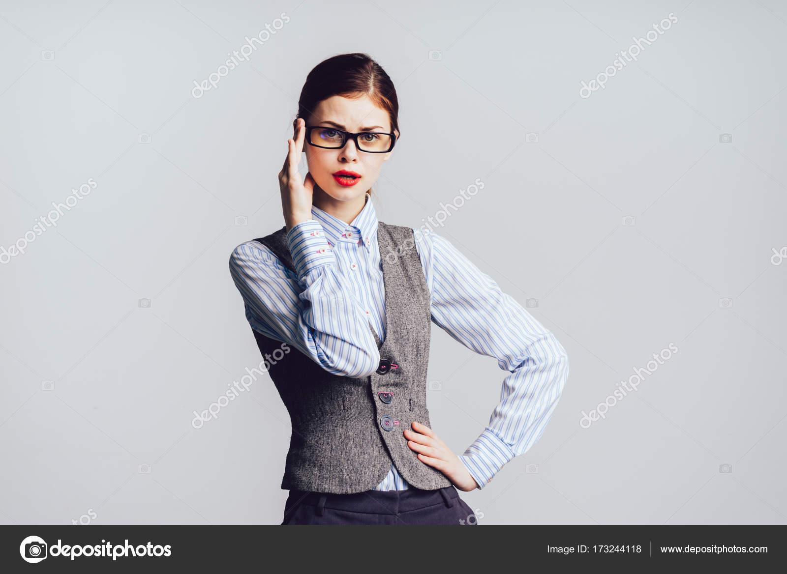 64ae987674d0 Elegante ragazza giovane seria in occhiali e vestiti dell ufficio in posa