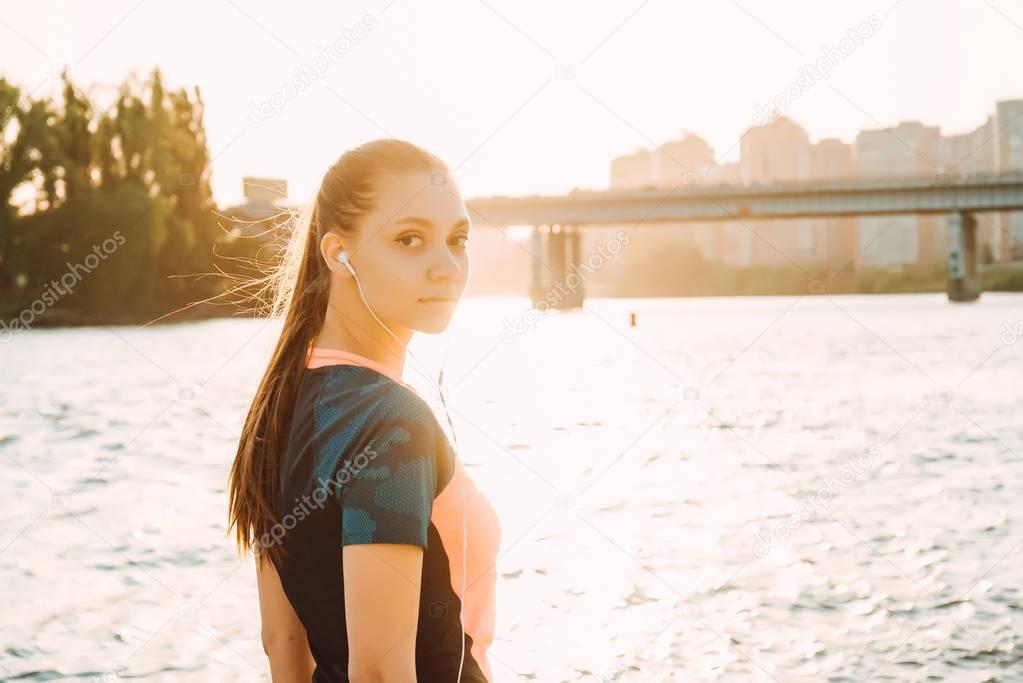 beautiful girl jogging on the waterfront listening to music on headphones