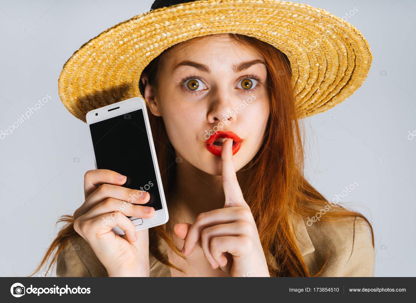 af4ca12a8b9 ένα αστείο κορίτσι με κόκκινα χείλη και σε ένα μεγάλο καπέλο κρατά ...