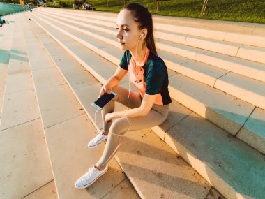 Girl after jogging sat down on the steps to relax and listen to music on headphones