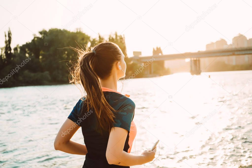 slim girl in sports clothes runs around the river, listening to music on headphones