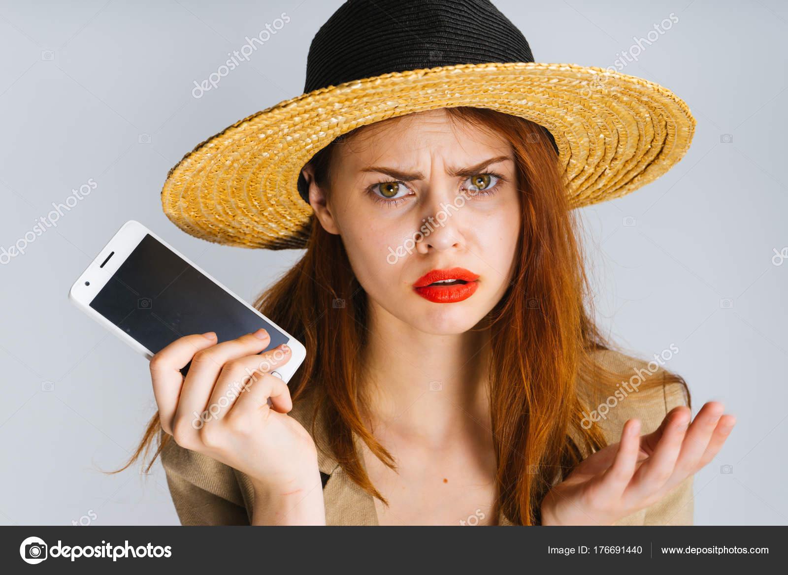 Triste Menina Ruiva Em Um Chapéu De Palha Detém Um Smartphone
