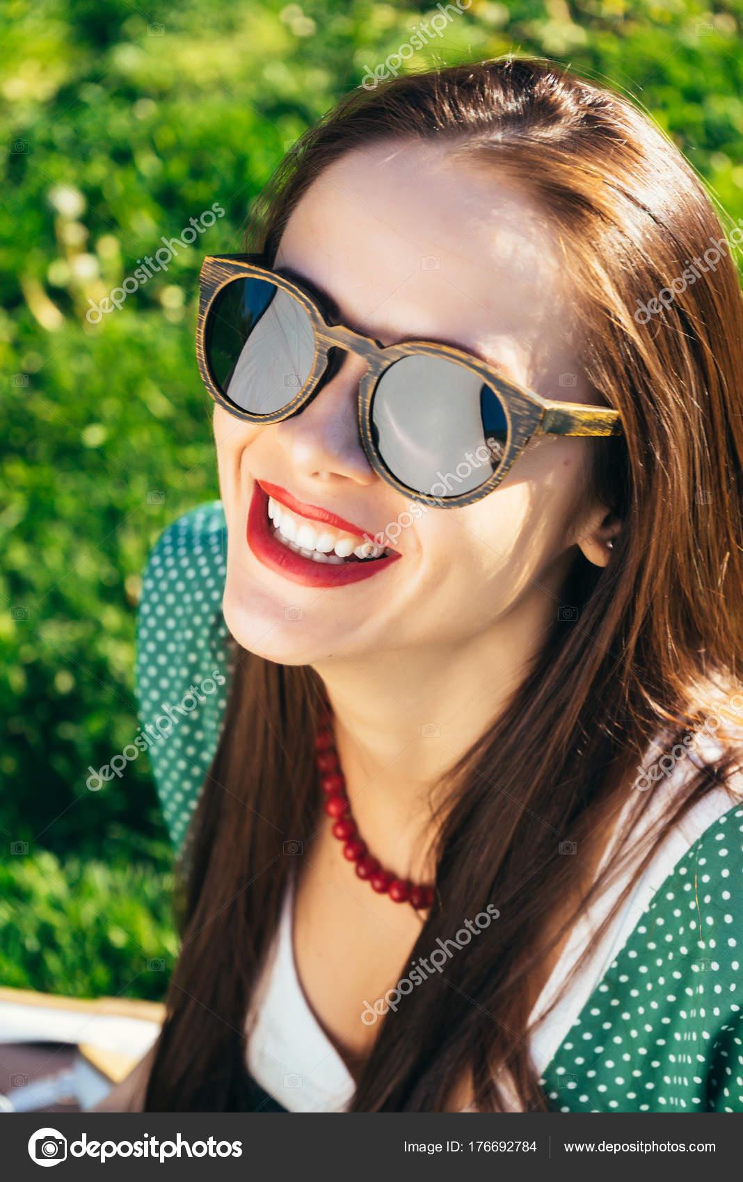 86fcbfcf31519 Close-up do rosto de mulher em óculos de sol, óculos de madeira ...
