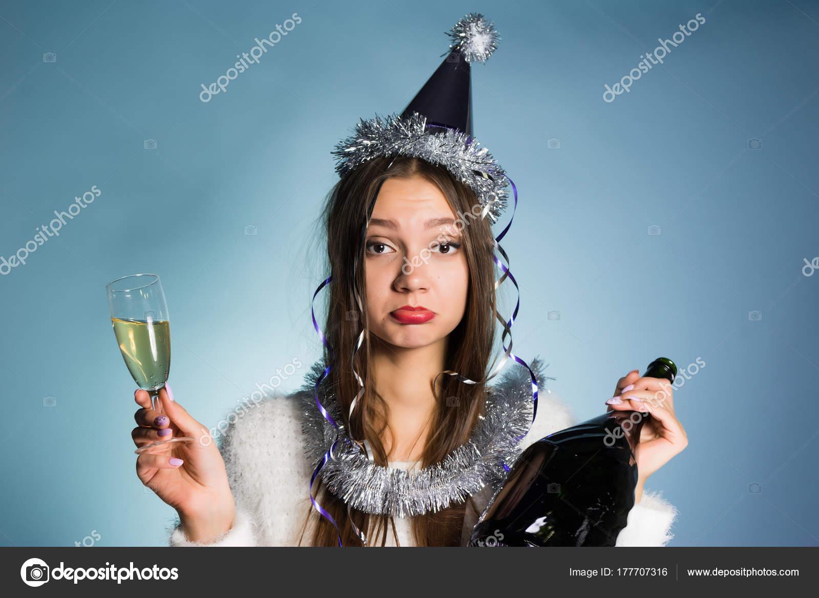 62a50746f9 Triste borracha chica celebra el año nuevo, es una botella y una copa de  champán