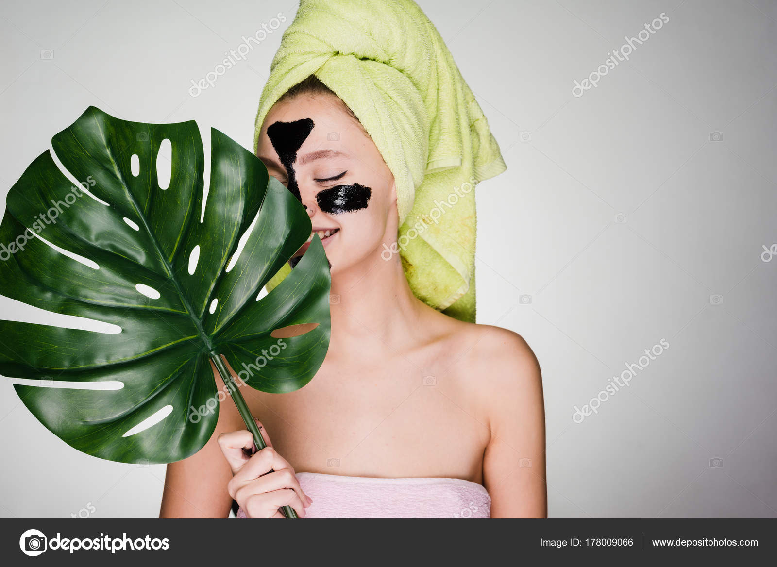 7c7de4cebc6 An attractive young girl with a green towel on her head covers her face  with a green leaf