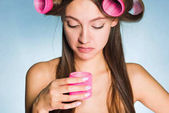 a young girl wants a fashionable hairstyle, holds in her hand large pink curlers