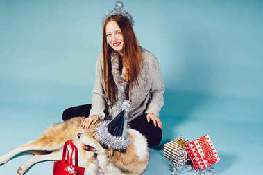 happy red-haired girl sits on the floor with her dog, waiting for the new year, Christmas atmosphere