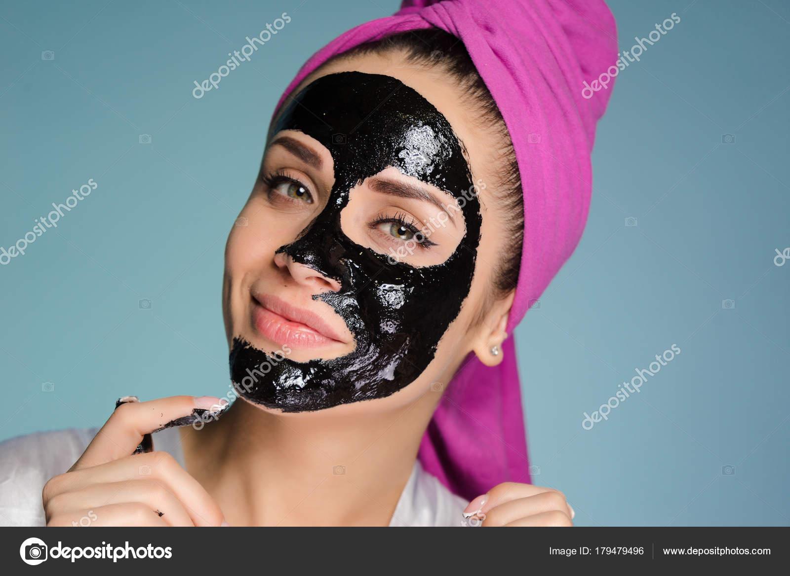 Jolie fille souriante avec une serviette rose sur sa tête a