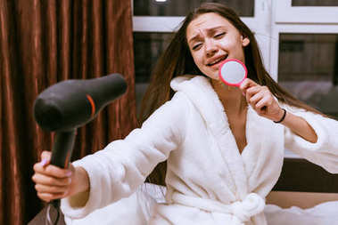 funny young girl dries her long hair with a hair dryer, sings in a comb