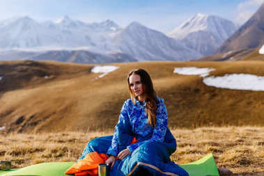young active girl sitting in a blue sleeping bag on a background of the Caucasian mountains