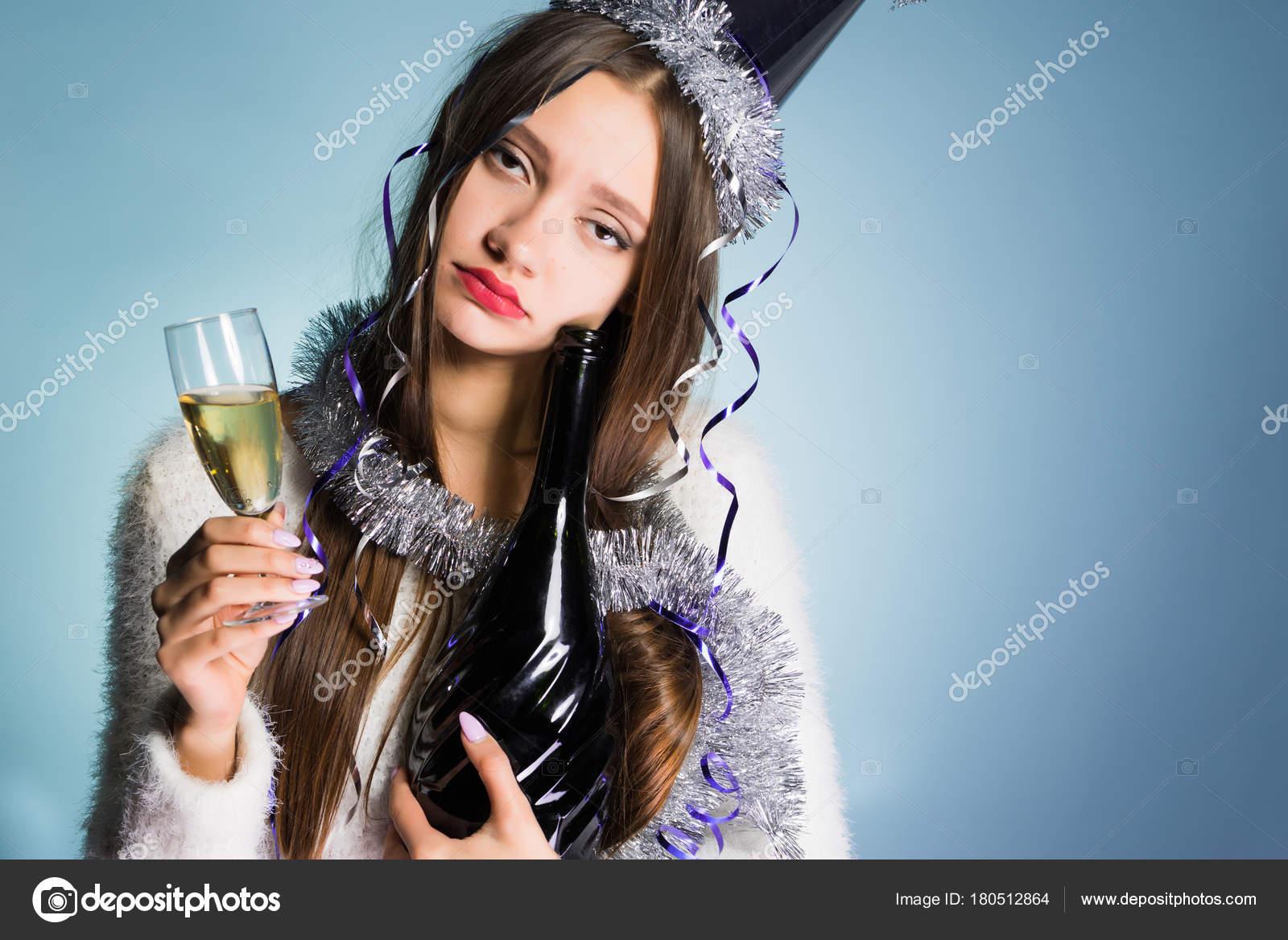 be43fdb517 Chica borracha joven triste en un casquillo celebra el año nuevo, mantiene  Champaña en las manos– imagen de stock