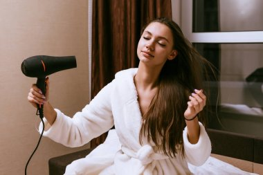a woman with long hair to dry them with a hair dryer