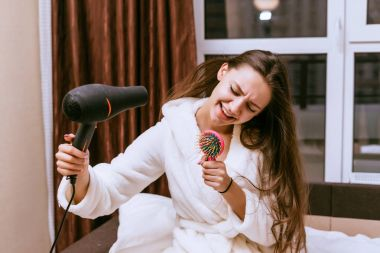 happy woman blowing her hair with a hair dryer