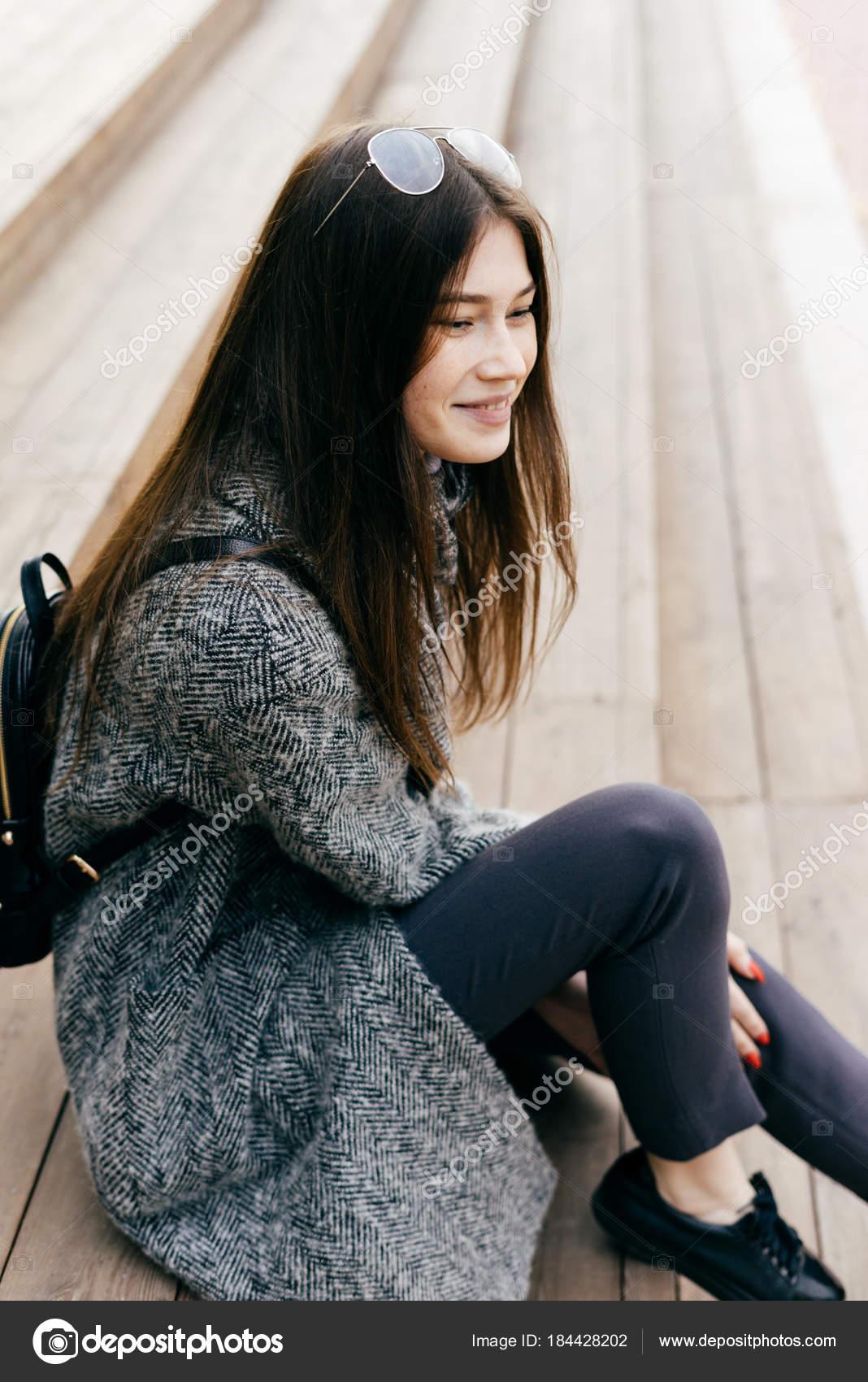 Städtischen schönes junges Mädchen mit dunklen Haaren in einem grauen  Mantel sitzt auf der Treppe und 69e67fe09d