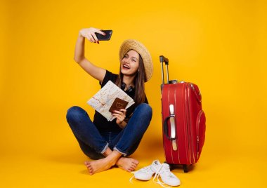 happy woman tourist holding a passport in hands and making selfie, vacation