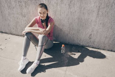 slim athletic young girl resting after street workout, stubbornly engaged in sports