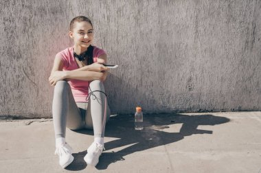 happy young girl sitting on the ground and resting after a long workout, restoring strength and energy, smiling