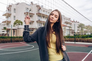 young long-haired girl exercising and stretching on outdoor sports field. playing sports