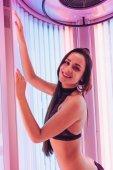 Fényképek boldog napozás a függőleges szolárium alatt ultraibolya sugárzás, mosolygós kislány