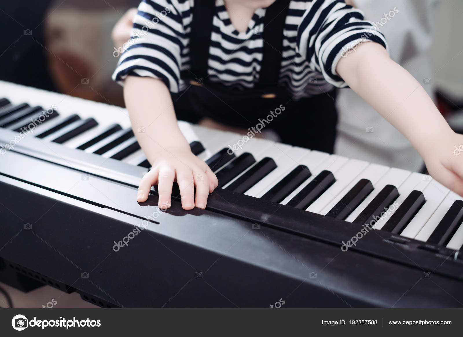 Friendly family, little baby boy playing the piano, studying the