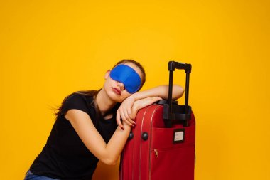 a young girl is sleeping on a large suitcase, in front of a mask to sleep, waiting for her plane, a long-awaited vacation
